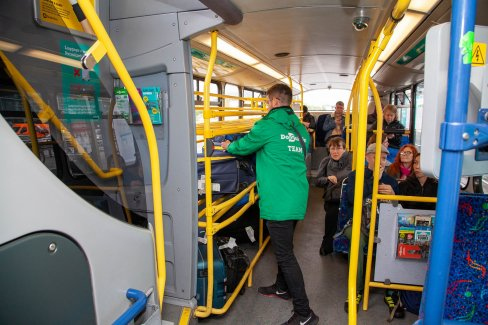 internal image of airlink bus with staff member helping load bags